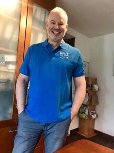 """Der Münchner Hüft-Spezialist Dr. Raimund Völker trägt das schön bestickte Polo-Hemd gern - und macht seinen Patienten damit """"Mut zur neuen Hüfte""""."""
